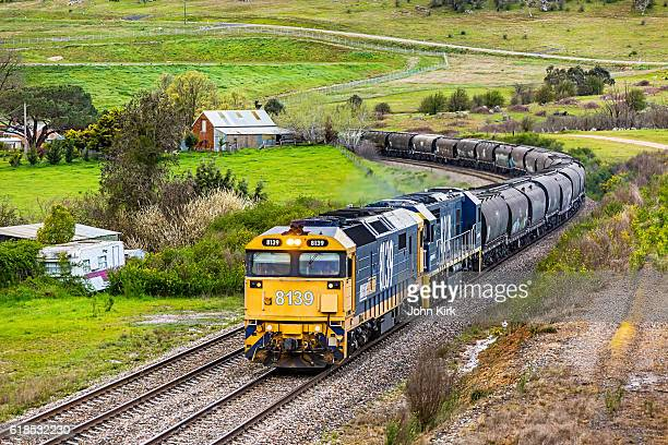 pacific national bulk grain train rounding bend in rural landscape - rail freight stock pictures, royalty-free photos & images