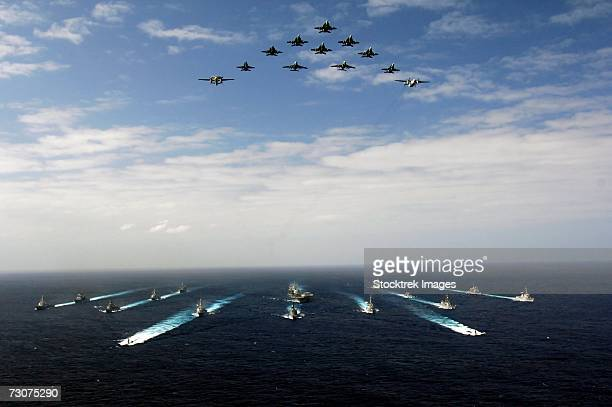pacific ocean (november 14, 2006) - aircraft assigned to carrier air wing five (cvw-5) fly over a group of 18 u.s. and japanese maritime self-defense force ships, at the conclusion the two nations' exercise annualex. - military ship stock pictures, royalty-free photos & images