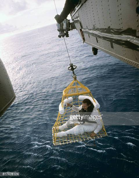 Apollo 13 astronaut John L Swigert Jr sits in a rescue basket as he is lifted aboard a recovery helicopter following splashdown