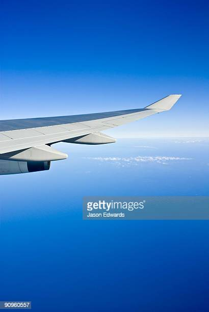 a jet airliner wings it's way across the pacific ocean on a clear day. - aerodinâmico - fotografias e filmes do acervo