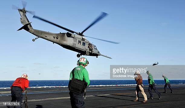 pacific ocean, november 10, 2012 - a u.s. air force hh-60g pave hawk helicopter lifts off the aircraft carrier uss nimitz. - aircraft carrier stock pictures, royalty-free photos & images