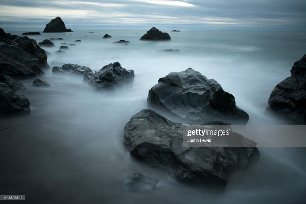 Pacific Ocean Swirls Around Dramatic Rock Formations Blue Horizon and Dramatic Storm Clouds : Stock Photo