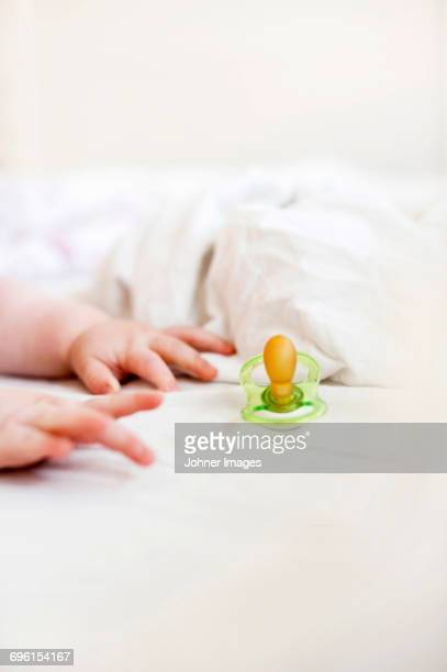 Pacifier and babys hands on bed