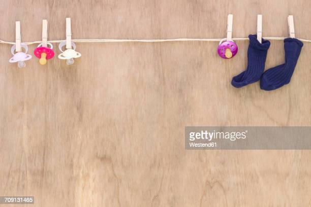 Pacifiers and babys socks on clothesline
