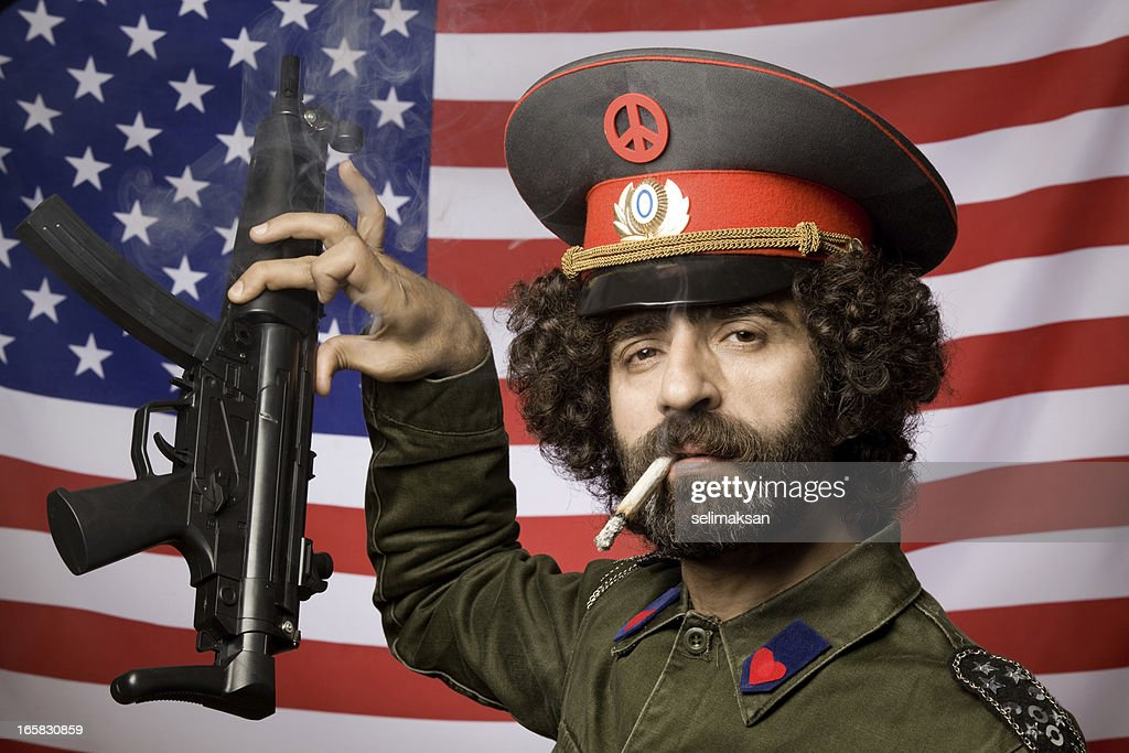 Pacifist in military uniform leaving his weapon before American flag : Stock Photo