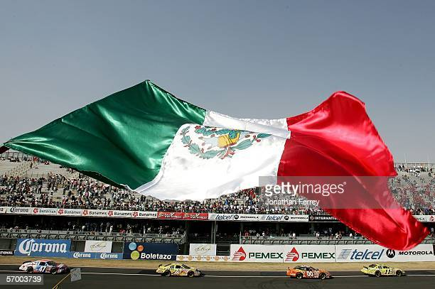 Pack of cars races beneath the Mexican flag during the NASCAR Busch Series Telcel-Motorola 200 on March 5, 2006 at Autodromo Hermanos Rodriguez in...