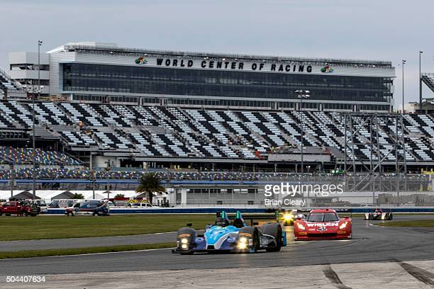A pack of cars races in front of the newly renovated stadium granstands during IMSA testing at Daytona International Speedway on January 10 2016 in...