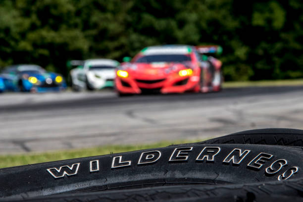 A Pack Of Cars Races Past Tire Barrier During The Michelin Gt Challenge Imsa Weathertech