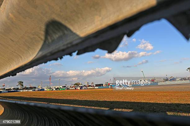 Pack of cars races under fluffy clouds in a blue Florida sky during the 12 Hours of Sebring at Sebring International Raceway on March 15, 2014 in...