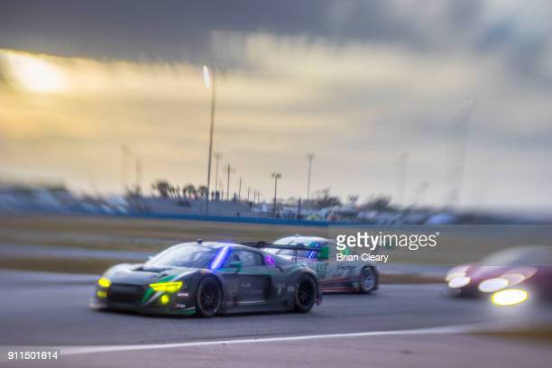 A pack of GT cars races on the track at sunrise during the Rolex 24 at Daytona IMSA WeatherTech Series race at Daytona International Speedway on...