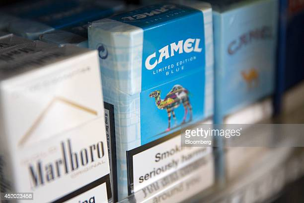 Pack of Marlboro cigarettes, left, manufactured by Philip Morris International Inc., a unit of Altria Inc., sits beside packs of Camel cigarettes,...