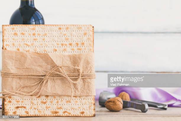 Pack of matzah or matza and Kosher red wine on a vintage wood background.Jewish Passover holiday composition with copy space and blurred background or bokeh.