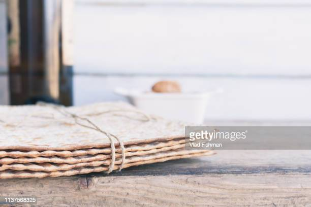 pack of matzah or matza and red kosher wine - happy passover stock pictures, royalty-free photos & images