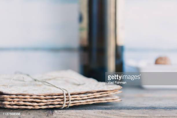pack of matzah or matza and red kosher wine - passover symbols stock pictures, royalty-free photos & images