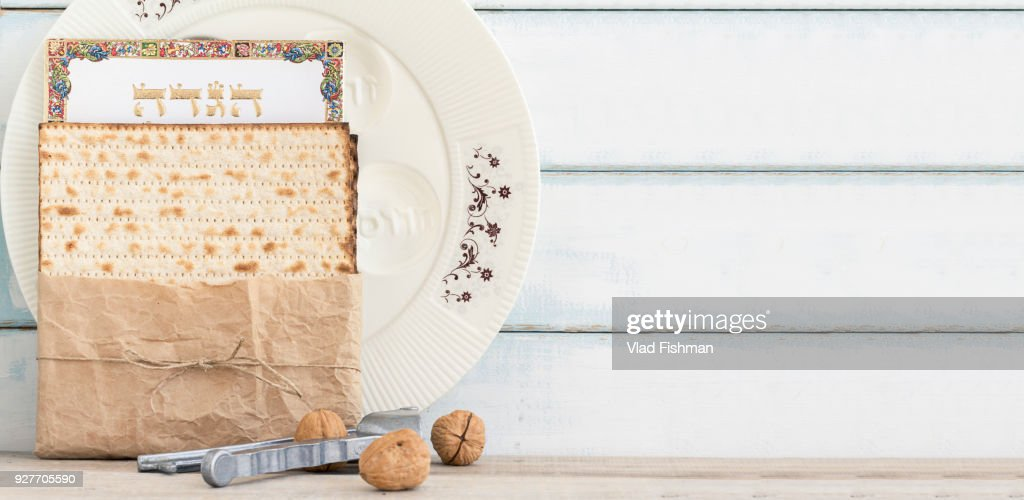 Pack of matzah or matza, Passover Haggadah and a whute passover seder plate on a vintage wood background. : Stock Photo