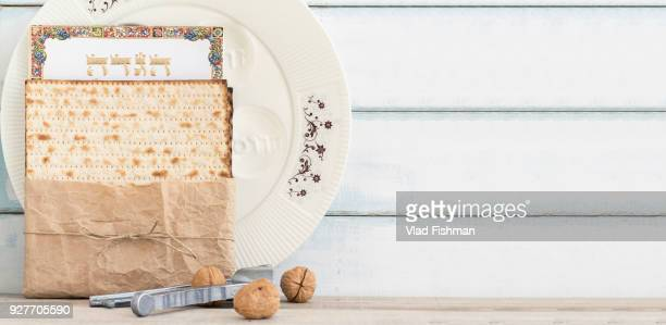 Pack of matzah or matza, Passover Haggadah and a whute passover seder plate on a vintage wood background.