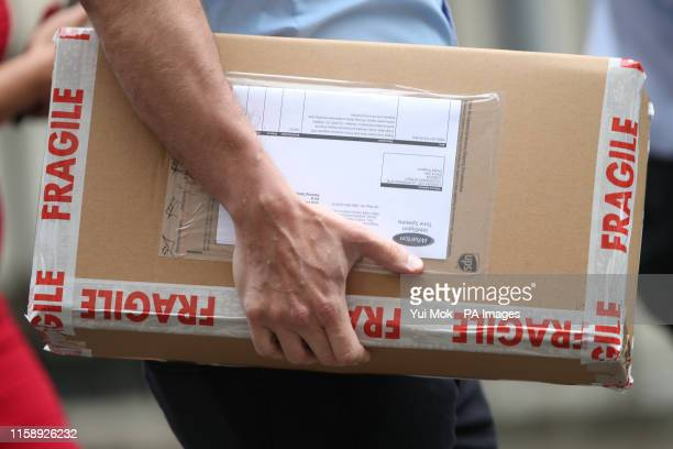 A package containing a digital countdown clock is carried in to 10 Downing Street in London