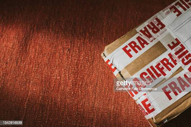 a package covered in fragile warning tape - sachet stock pictures, royalty-free photos & images
