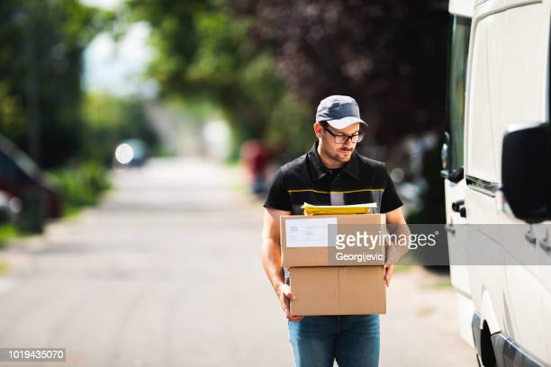 package delivery - postal worker stock pictures, royalty-free photos & images