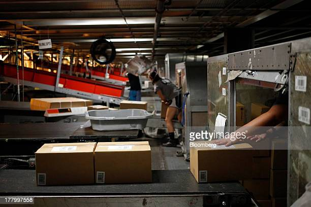 A package handler unloads incoming boxes during United Parcel Service Inc Worldport overnight shipping operations at Louisville International Airport...