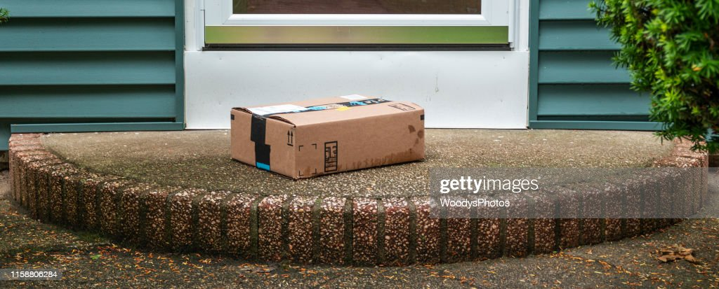 Package left out in the rain exposed on a front porch : Stock Photo