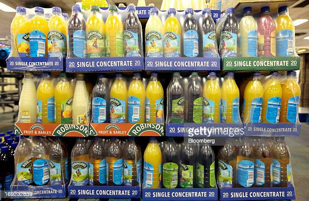 Packaged bottles of Robinsons squash drink produced by Britvic Plc sit wrapped in plastic alongside the production line at the company's factory in...