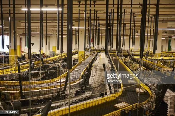 Packaged orders pass along automated conveyor belt systems at Amazoncom Inc's new fulfillment center in Kolbaskowo Poland on Friday Feb 16 2018 Both...