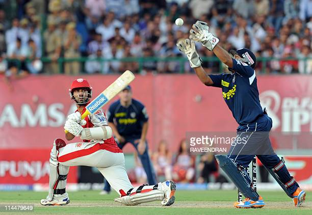 PACKAGEKings XI Punjab batsman Dinesh Karthik watches as Deccan Chargers wicketkeeper Kedar Devdhar attempts a catch during the IPL match between...