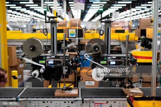 Packages are labeled at a SLAM or scan label apply and manifest station during a tour of Amazon's Fulfillment Center September 21 2018 in Kent...