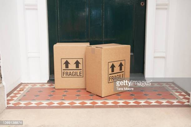 packages left by door at house - parcel stock pictures, royalty-free photos & images