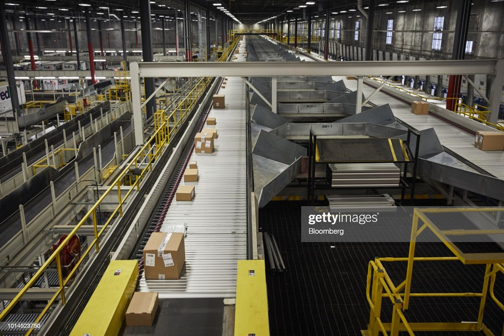 Packages move along a conveyor belt at the FedEx Corp. Ground distribution center in Jersey City, New Jersey, U.S., on Tuesday, Aug. 7, 2018. FedEx is heading into fiscal 2019 running on all cylinders, with revenue growth and margin expansion expected across all three of its segments. Photographer: Marc McAndrews/Bloomberg via Getty Images
