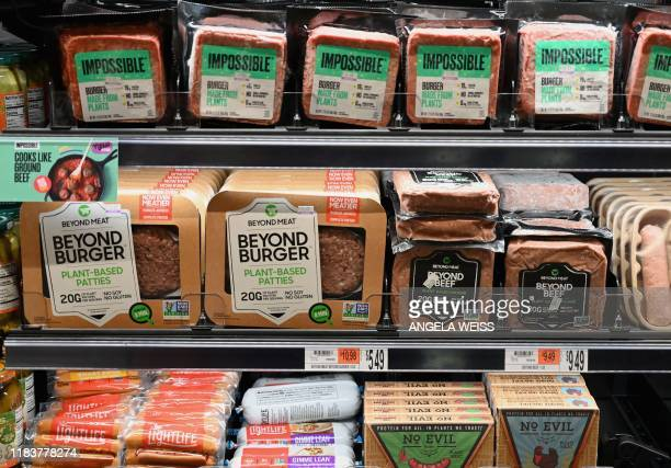 Packages of Impossible Burger and Beyond Meat sit on a shelf for sale on November 15 2019 in New York City Vegetarian alternatives to burgers and...