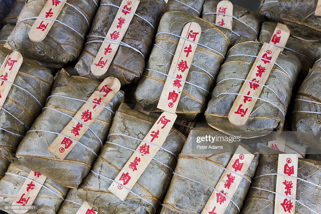 Packages of pork rolled in rice and wrapped in leaf : Stockfoto