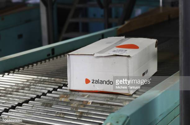 Packages of Zalando clothing company stand on a conveyor for delivery at the German postal service DHL transit center on December 5, 2018 in...
