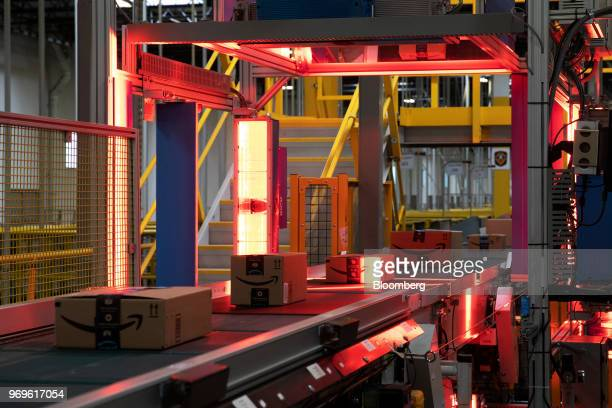 Packages pass a scanner while moving along a conveyor at the Amazoncom Inc fulfillment center in Robbinsville New Jersey US on Thursday June 7 2018...