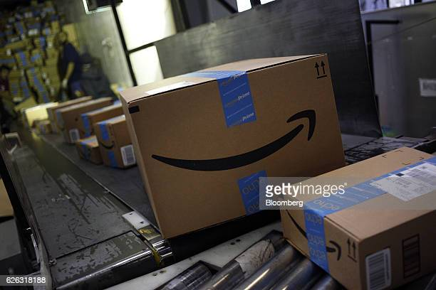 Packages shipped from Amazoncom Inc move along a conveyor belt at the United Parcel Service Inc Chicago Area Consolidation Hub facility in Hodgkins...