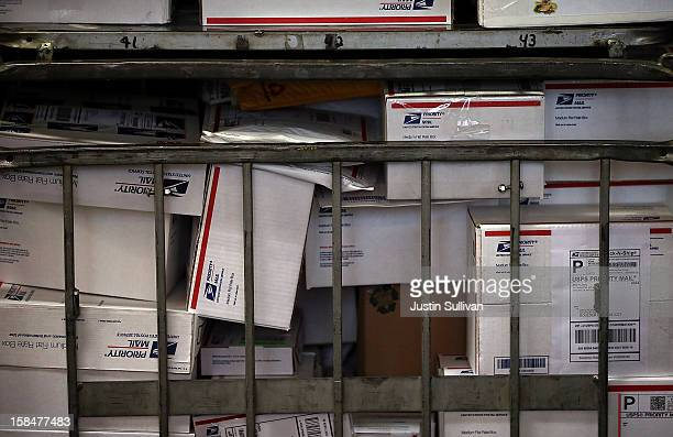 Packages sit in a bin at the United States Post Office at Rincon Center on December 17 2012 in San Francisco California Customers line up at post...
