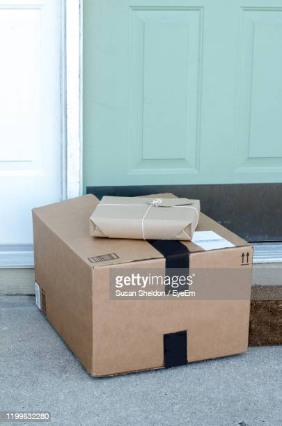 packages waiting on the doorstep wrapped in brown paper and tied with string - gifts stock pictures, royalty-free photos & images
