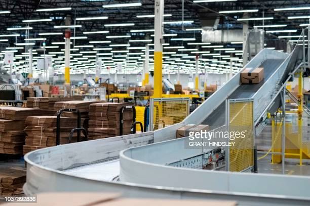 Packed and labelled goods move on the sortation conveyor during a tour of Amazon's Fulfillment Center September 21 2018 in Kent Washington