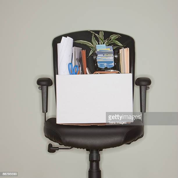 packed box on office chair - downsizing unemployment stock pictures, royalty-free photos & images