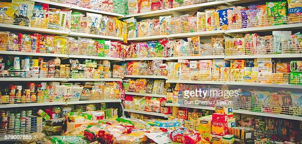packed food in shelf for sale at supermarket - rack stock pictures, royalty-free photos & images
