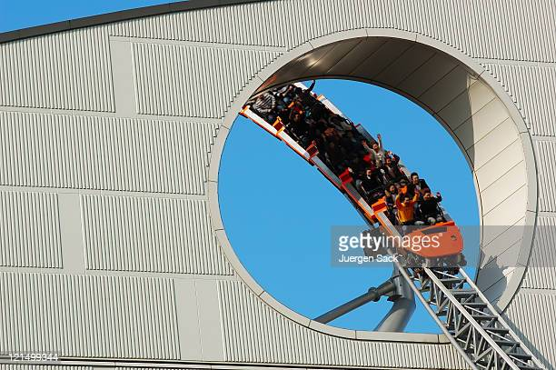 Packed red roller coaster going through a circular opening