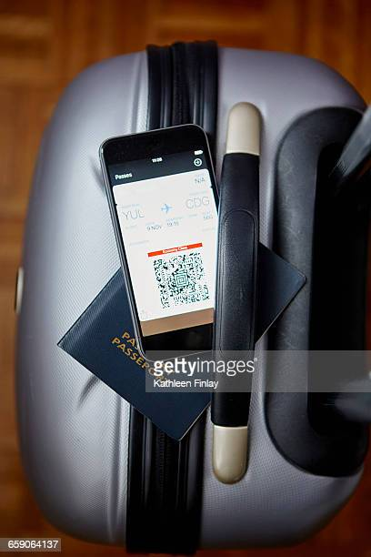 Packed suitcase with passport and smartphone balanced on top, overhead view