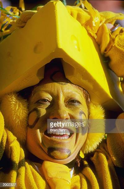 Packers Fan dressed in yellow wears a cheese hat as she cheers for the Packers during a game against the San Francisco 49ers at Lambeau Stadium...