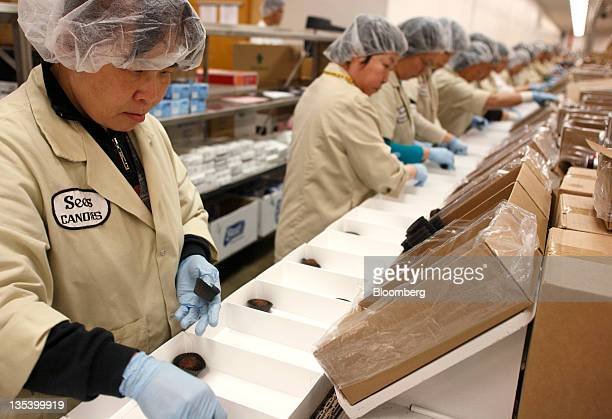 Packers fill boxes of chocolate on the production line at the See's Candies Inc packing facility in South San Francisco California US on Thursday Dec...