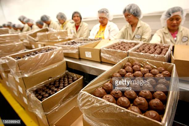 Packers fill boxes of chocolate on the production line at the See's Candies Inc. Packing facility in South San Francisco, California, U.S., on...