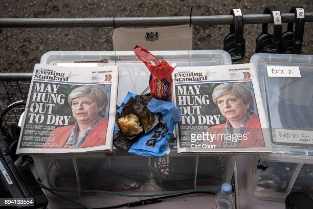 A packet of biscuits and a half eaten muffin are placed between copies of the Evening Standard that are being used for reference by radio journalists...