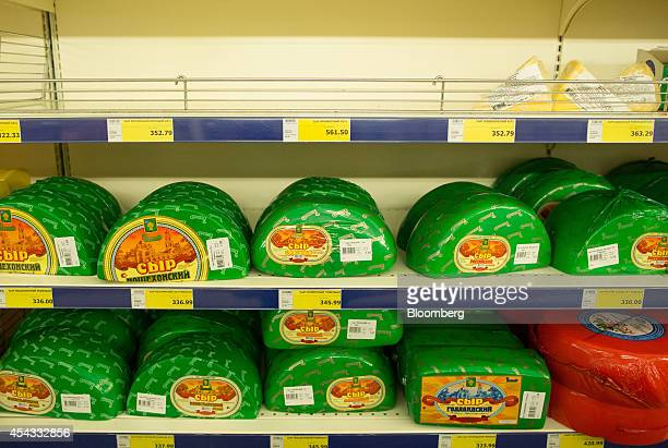 Packets of processed cheese sit for sale beneath empty shelves inside a Metro Cash Carry store the Russia unit of Metro AG in Moscow Russia on Friday...
