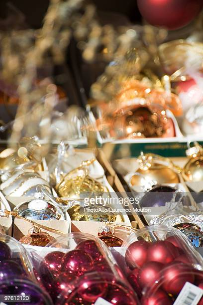 Packs of Christmas ornaments on display in shop, close-up