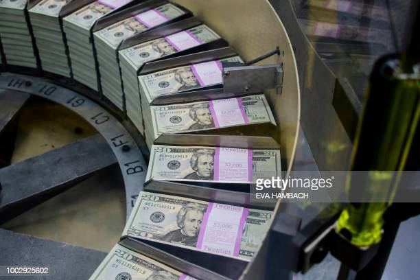 Packs of freshly printed 20 USD notes are processed for bundling and packaging at the US Treasury's Bureau of Engraving and Printing in Washington DC...
